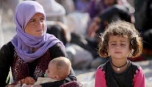 Een Iraakse Yezidi vrouw zit met haar kinderen in het Bajid Kandala kamp in de buurt van de rivier de Tigris, in het westen van de provincie Dohuk van Koerdistan, waar ze hun toevlucht zochten na de vlucht voor het oprukken van de jihadisten van de Islamitische Staat in Irak op 13 augustus 2014. (Photo credit: AFP / AHMAD AL-RUBAYE)